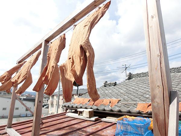 屋根の上では気持ちよさそうに柿渋染めの服が風になびいて